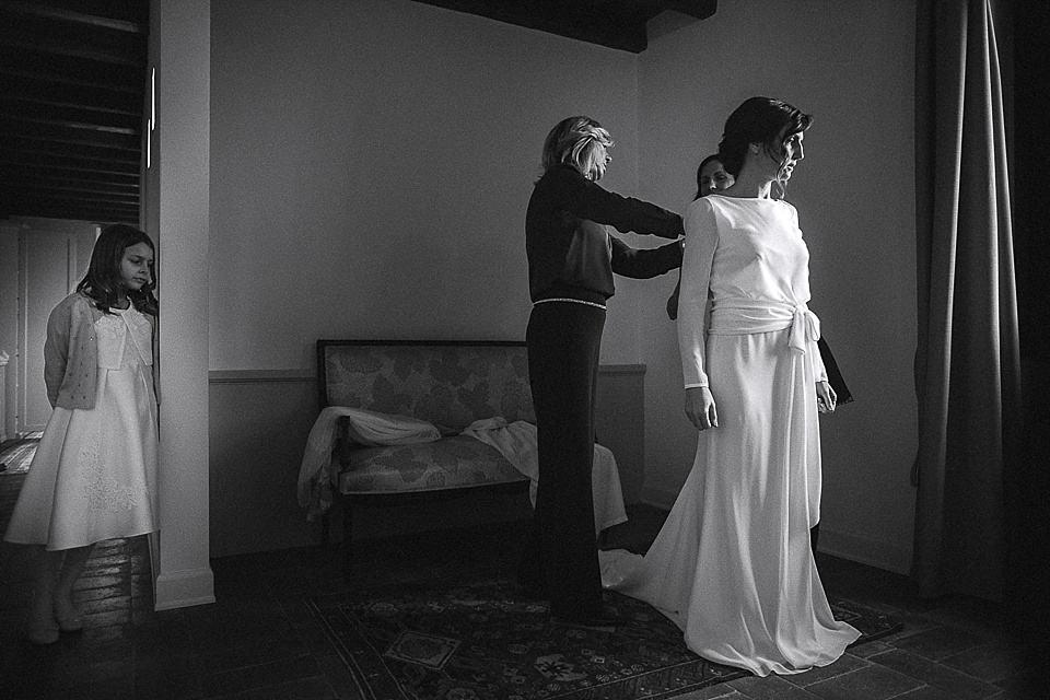 Fotografia della sposa mentre indossa l'abito del matrimonio